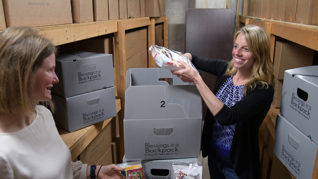 Diana Schmidt, property and casualty consultant and principal at Hausmann-Johnson Insurance, works with Amanda Busche, business development and real estate associate at VJS Construction Services, to unpack food.