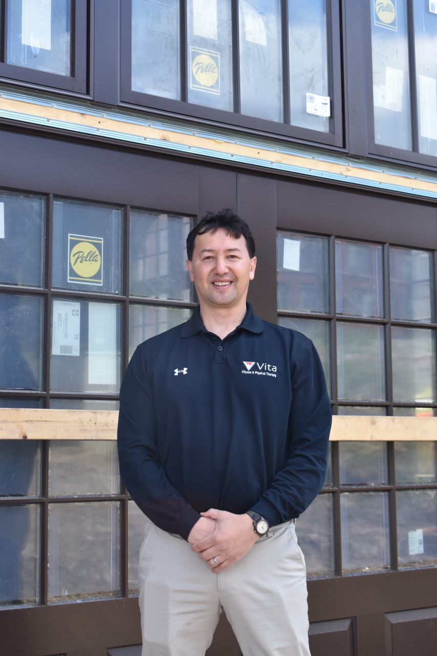 Tommy Grabowski of Vita Health & Fitness standing in front of the new gym space at the M10 Powerhouse building.