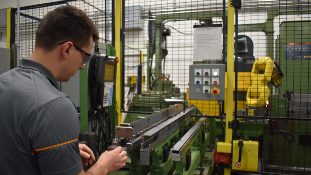 American Friction Welding general manager Casey Fischer loads a component into an automated cell.