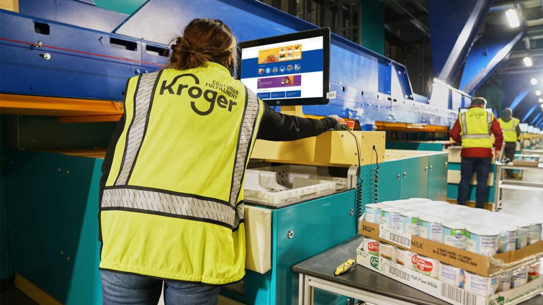 Employees operating technology at a Kroger customer fulfillment center.