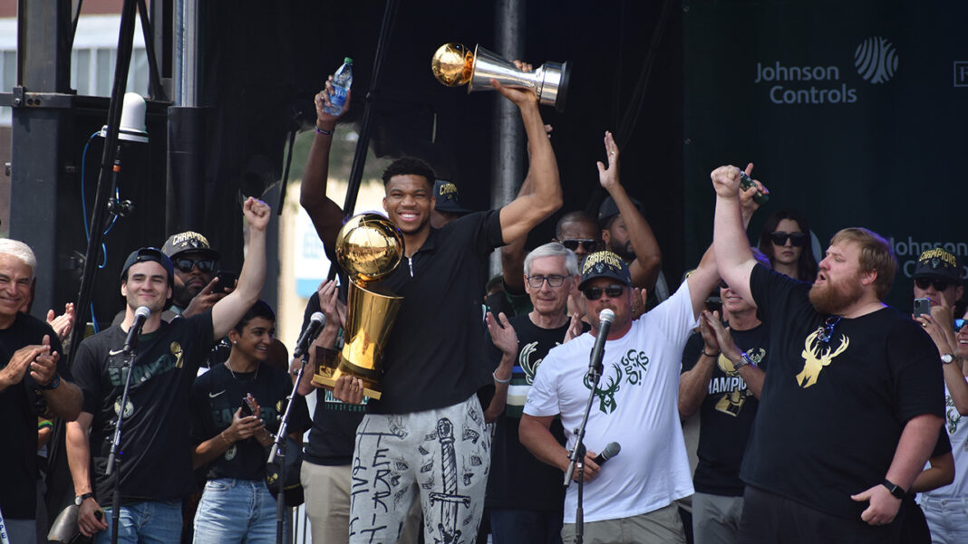 Giannis Antetokounmpo holds the Larry O'Brien NBA Championship trophy and his NBA Finals MVP trophy at the Bucks NBA championship celebration.