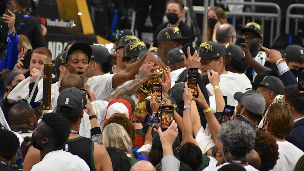 Milwaukee Bucks players embrace the Larry O'Brien NBA Championship Trophy.