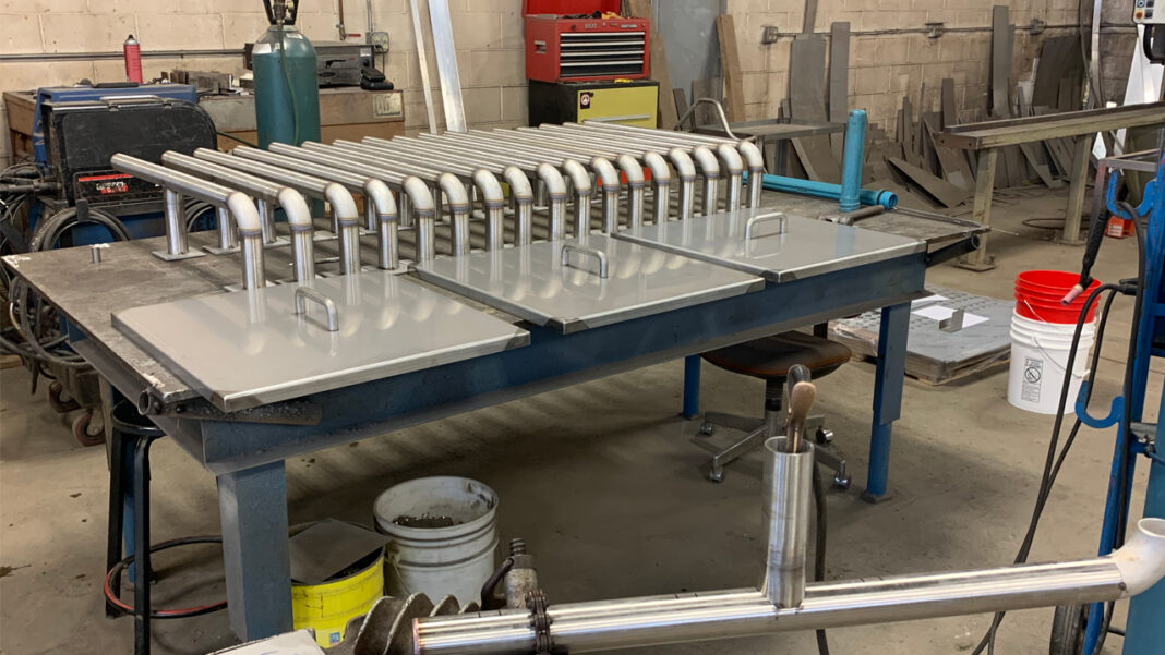 3Up Metal Works fabricated stainless steel hangers designed for pipe runs that move product through a food and beverage facility.