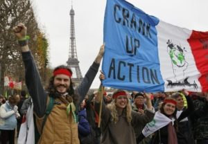"""Environmentalists hold a banner which reads, """"Crank up the Action"""" at a protest demonstration near the Eiffel Tower in Paris, France, as the World Climate Change Conference 2015 (COP21) continues near the French capital in Le Bourget, December 12, 2015. REUTERS/Mal Langsdon - RTX1YD4F"""
