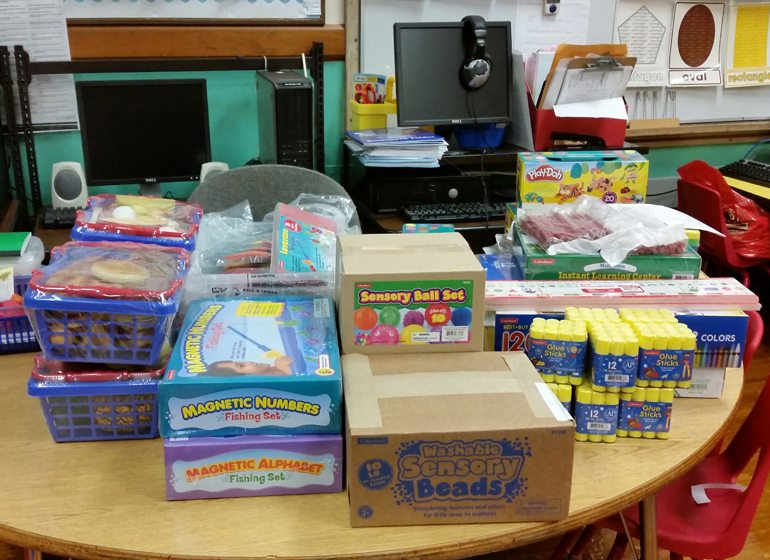 Around $4,000 worth of school supplies, equipment and learning materials cover a table and line a wall of Schlueter's classroom.