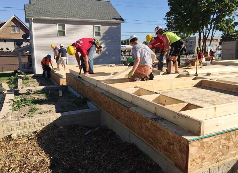 "More than 50 volunteers from Joy Global and Catholic Financial Life assist Milwaukee Habitat for Humanity in a ""Blitz Build"" in the city's Washington Park neighborhood to frame three new homes in a week."