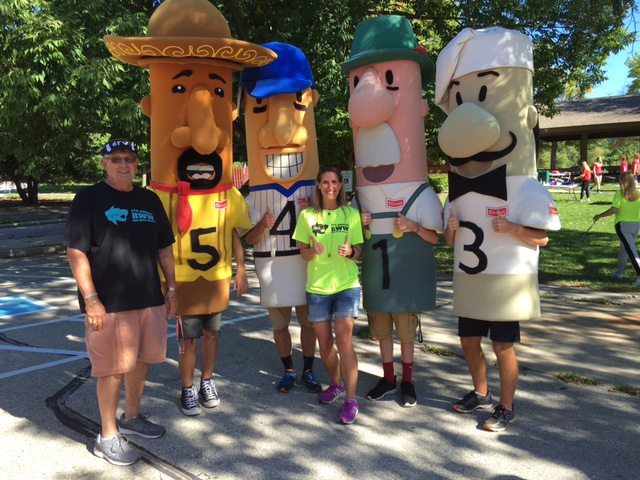 Cara Olson (middle) who organizes the annual Run With Wolfes golf outing and run, flashes two thumbs up with the Milwaukee Brewers racing sausages.