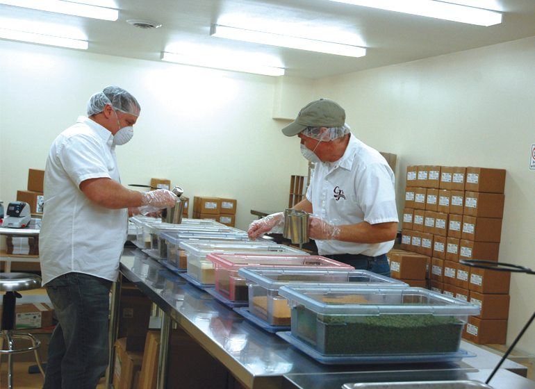 Alan Swan and his brother Chad measure spices at their Oconomowoc production facility.