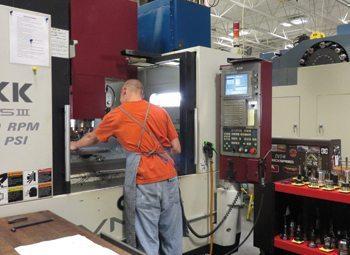 Reich Tool & Design  employee Jason Woiak sets a tool in a CNC machine.
