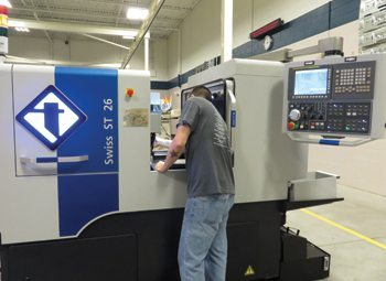 Mike Fiduccia makes an adjustment on Reich Tool & Design's new Swiss turning machine.