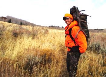 Ogurek, dressed in blaze orange hunting gear, hikes on a plateau in northwest Colorado.