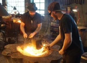 Kent Knapp (left) works at the forge in his shop in the Third Ward. Photo Credit: History.