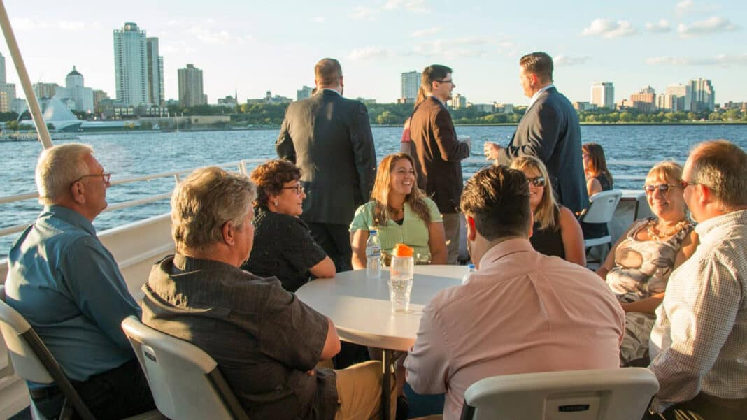 Attendees socialize on the back deck of Milwaukee River Cruise Line's Harbor Lady vessel.