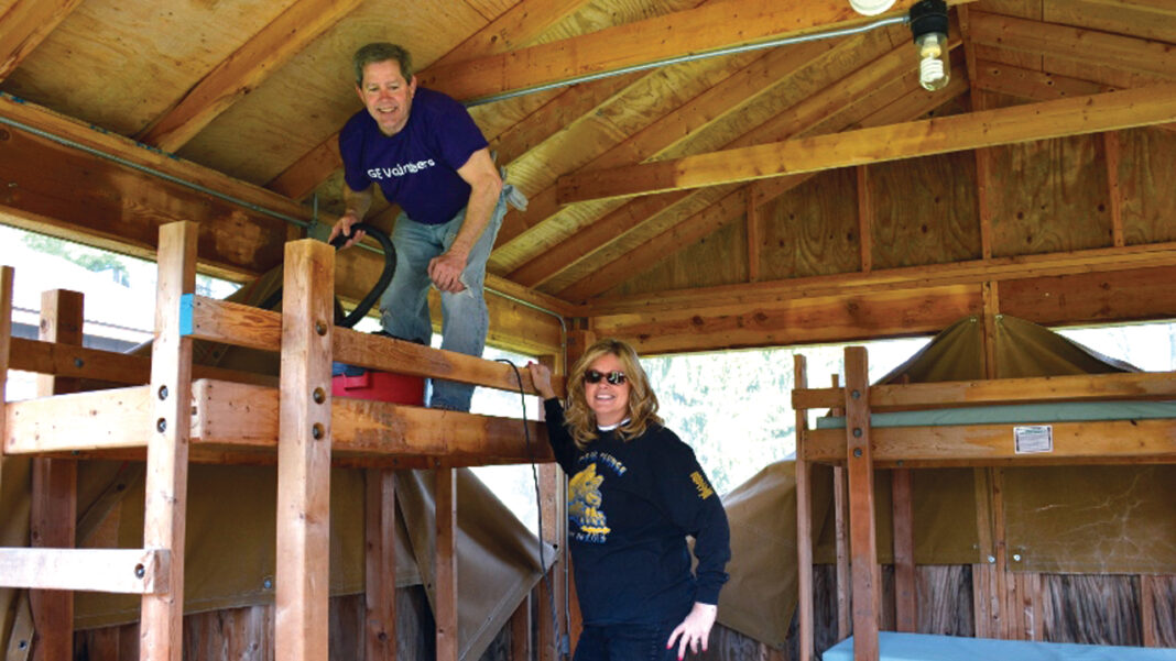 GE Healthcare employees cleaning up a cabin at a Girl Scouts camp during an annual day of service.