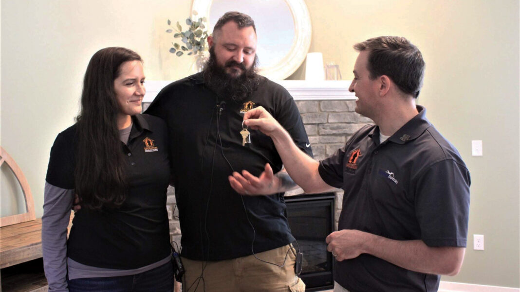 Jessica and Tyson Cole are handed the keys to their new Menomonee Falls home from David Belman, president of Waukesha-based Belman Homes.